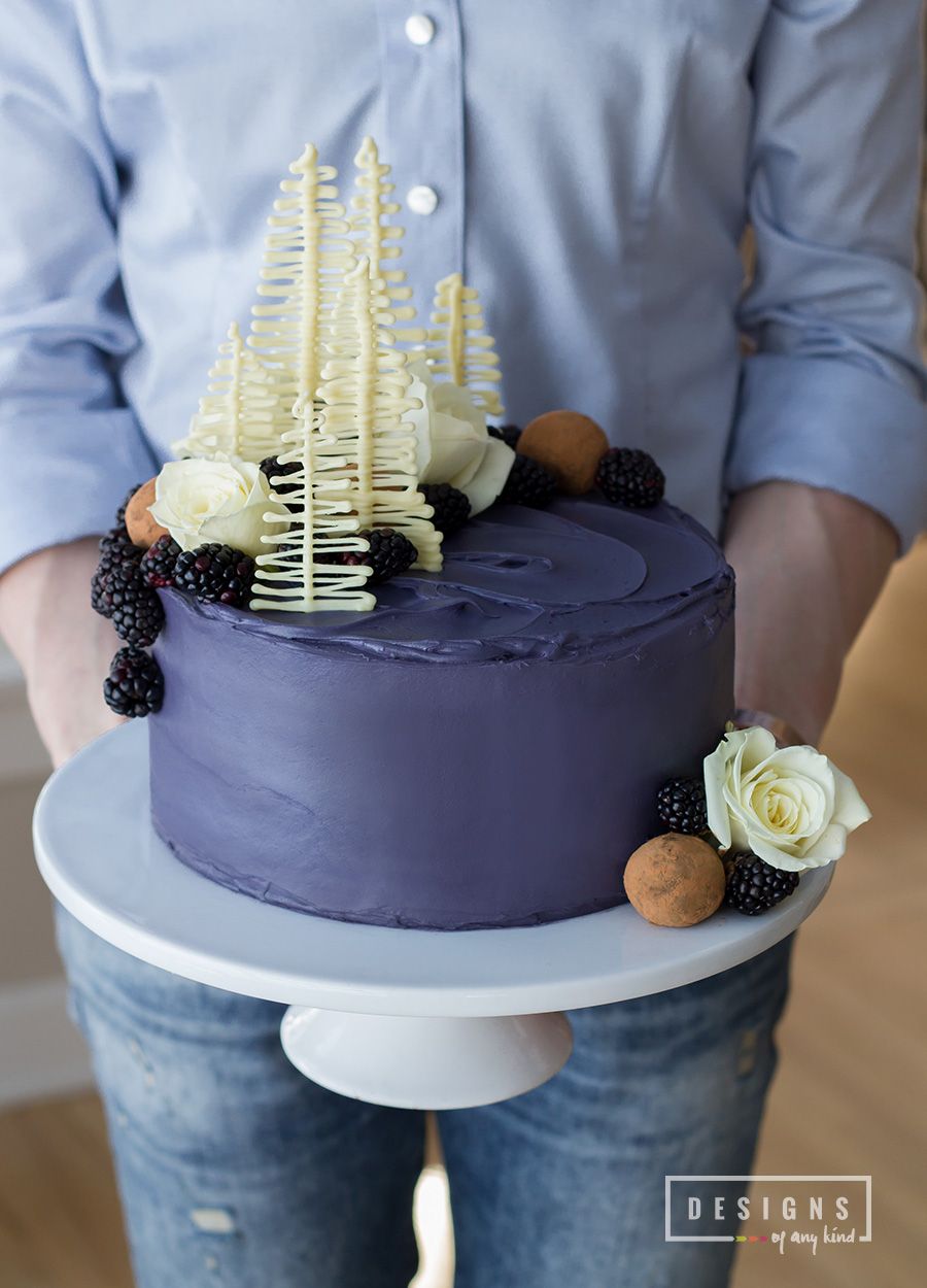 Four layers of rich, chocolate cake, filled with blackberry + blackpepper buttercream and topped with blackberries, chocolate truffles, white chocolate trees and roses. Find the recipe at designsofanykind.com