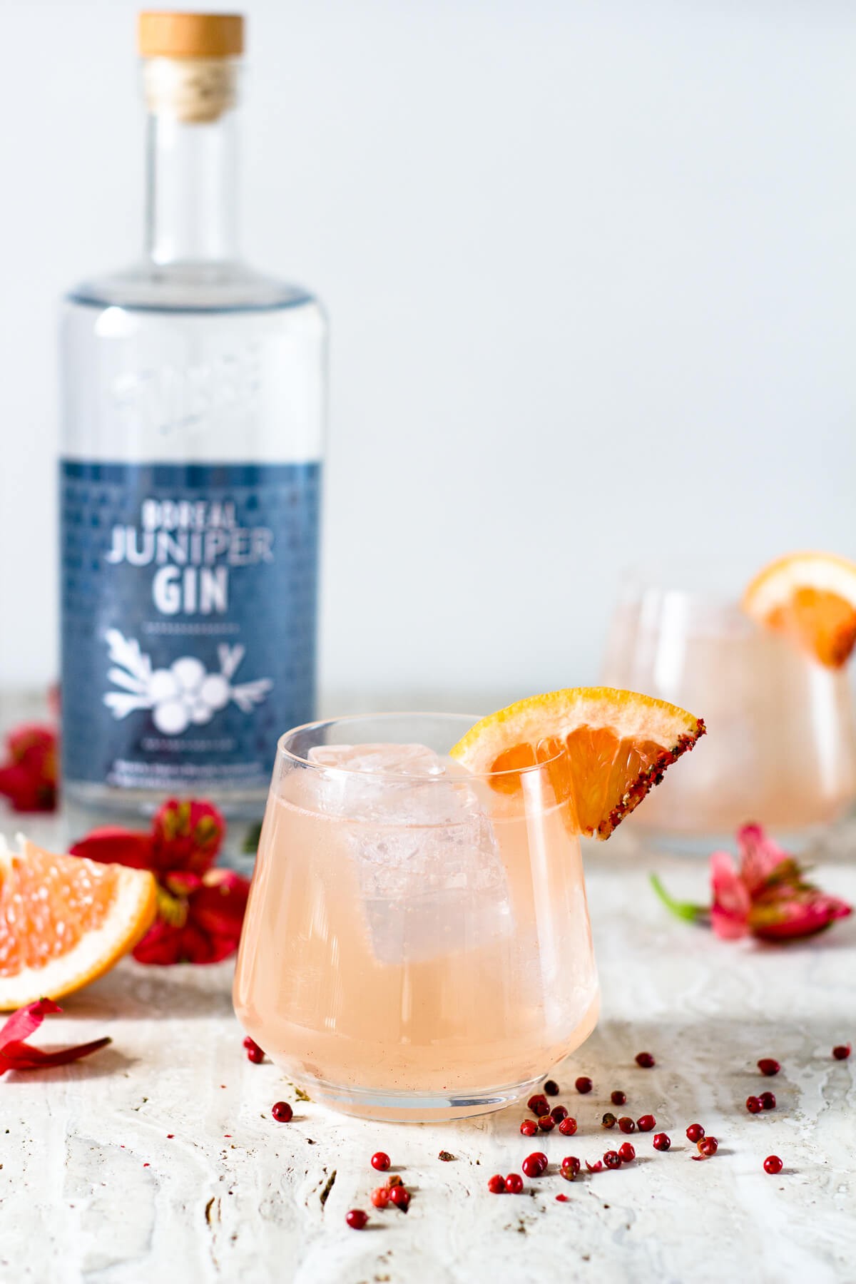 Whether sipped by the beach or on a porch this Grapefruit Pink Peppercorn Gin & Tonic is the most refreshing summer cocktail you'll ever have. Made with freshly squeezed grapefruit juice, pink peppercorn simple syrup, tonic water, and our favorite hand-crafted gin from Vikre Distillery. Recipe at www.designsofanykind.com