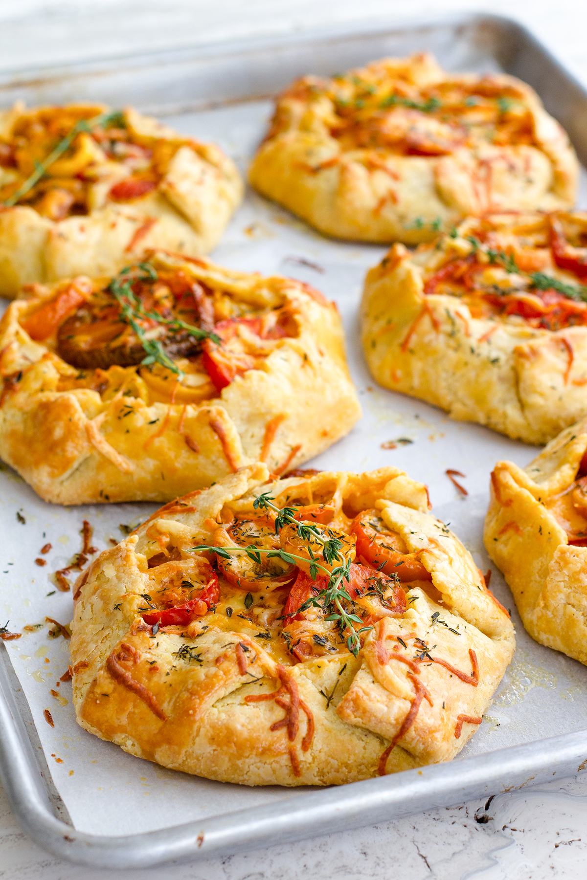Tender cornmeal crust cradles garden fresh tomatoes, thyme, cheddar and gouda in a savory galette that's ideal for a weekend brunch or intimate gathering. Herbed Tomato Galette recipe at www.designsofanykind.com
