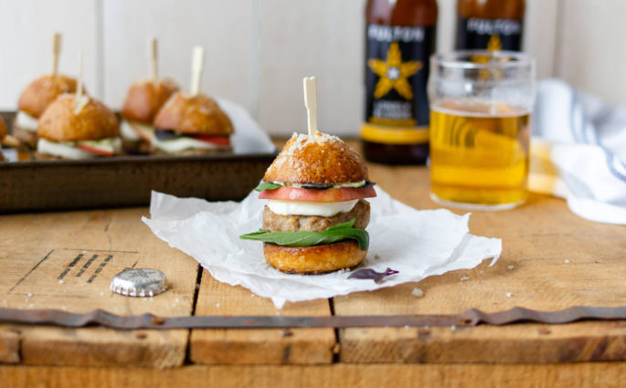 These flavorful mini turkey burgers are made with peaches, mozzarella, basil aioli and served on a mini pretzel bun. They make the perfect appetizer for game day or summertime party. Recipe at www.designsofanykind.com